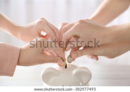 Hands putting coin into piggy bank at the table - stock photo
