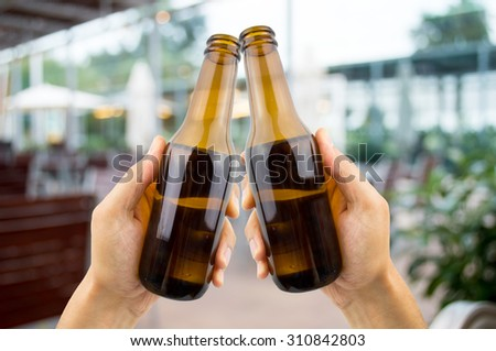 hands raised toasting with beer at the terrace bar in summer time - stock photo