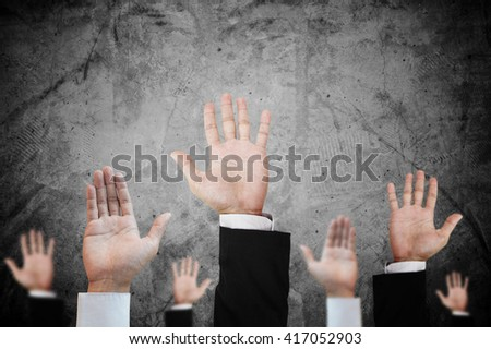 Hands raising upward on concrete background, abstract concept and ideas - stock photo