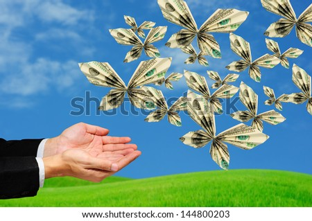 hands releasing origami butterfly made from 100 US Dollar banknotes - stock photo