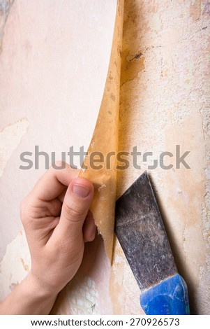 hands removing old wallpaper - stock photo