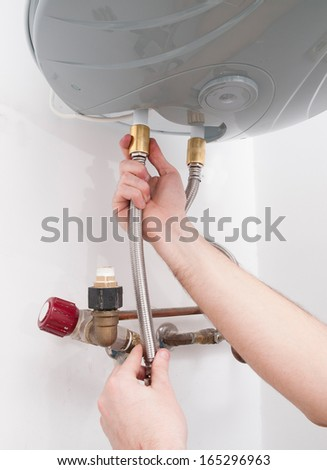 Hands repairing the plumbing pipes of an electric boiler. - stock photo