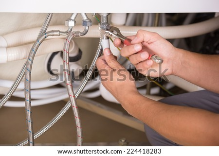 Hands repairing the plumbing pipes of an electric boiler with a spanner. Close-up. - stock photo
