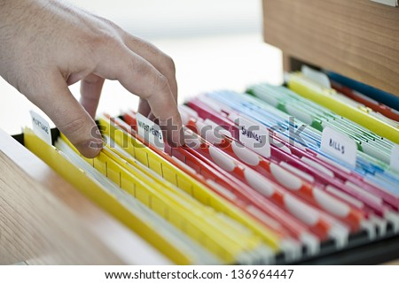 Hands searching through file folders with personal finance documents - stock photo