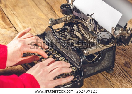 Hands secretary, writing on an old typewriter. - stock photo