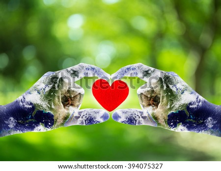hands shaped heart with world map - elements of this image furnished by NASA - stock photo