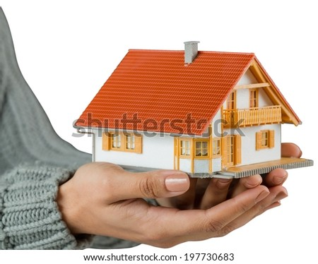 Hands showing a miniature model home on white background - stock photo