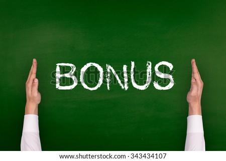 Hands Showing BONUS on Blackboard - stock photo