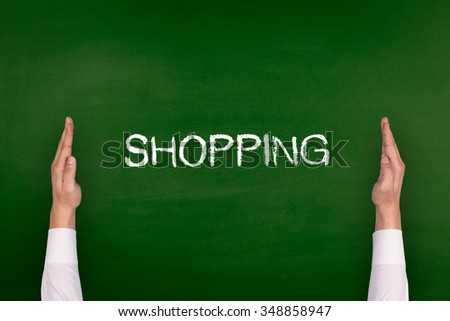 Hands Showing SHOPPING on Blackboard - stock photo