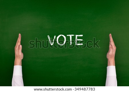 Hands Showing VOTE on Blackboard - stock photo