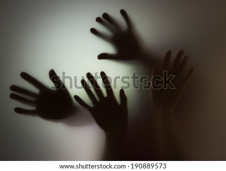 hands silhouette behind glass  - stock photo