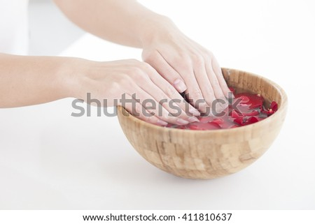 Hands Spa.Manicure concept. Women hands in wooden bowl with roses petals  - stock photo
