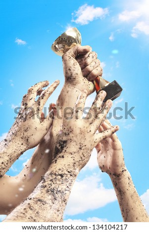 Hands squeeze the cup winner against lightning blue sky. - stock photo
