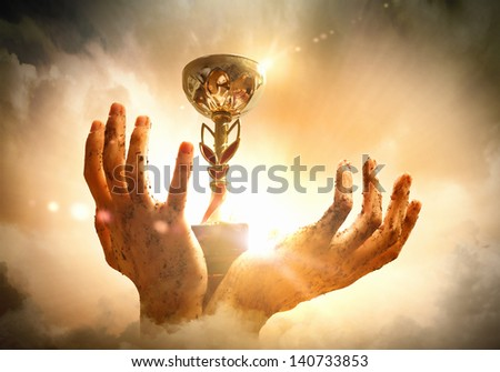 Hands squeeze the cup winner against lightning dark sky. - stock photo