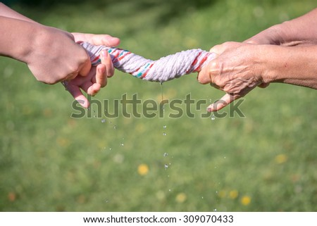 Hands squeeze wet fabric on a grass background - stock photo
