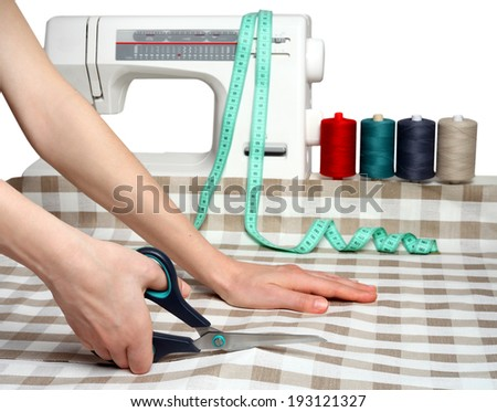 Hands tailor scissor fabric against the background of the sewing machine and accessories. - stock photo