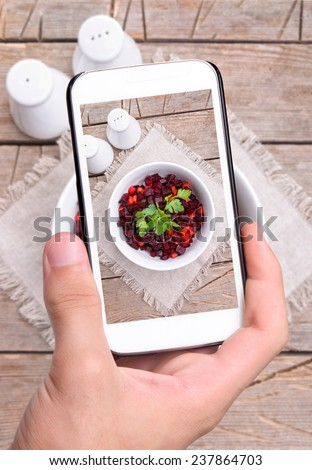 Hands taking photo beet salad with smartphone - stock photo