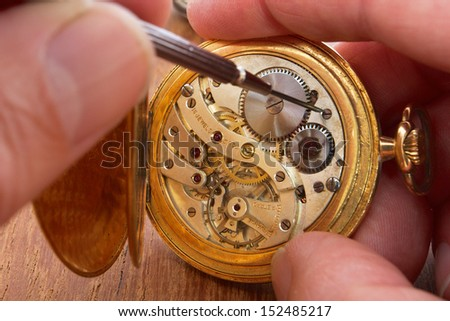 hands that repair an old pocket watch - stock photo