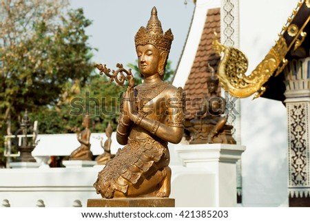 Hands together of calm Buddha with metal crown. Sculpture past the entrance of a Thai temple in Chiang Mai  - stock photo