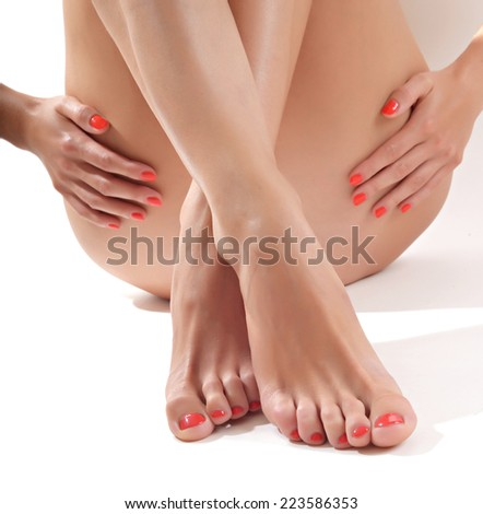 Hands touching beautiful woman's legs, isolated on white - stock photo
