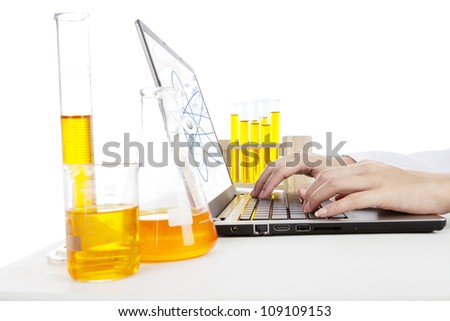 Hands typing on laptop computer doing an experiment of chemical particle - stock photo