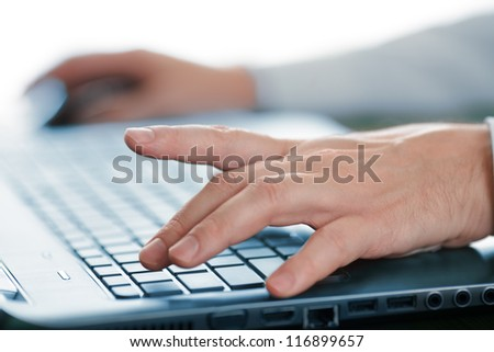 Hands typing on laptop keyboard - stock photo