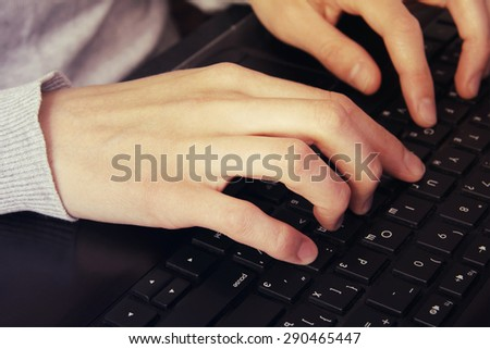 Hands typing on laptop keyboard toned vintage style - stock photo