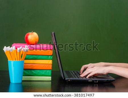 Hands typing on notebook near empty green chalkboard - stock photo