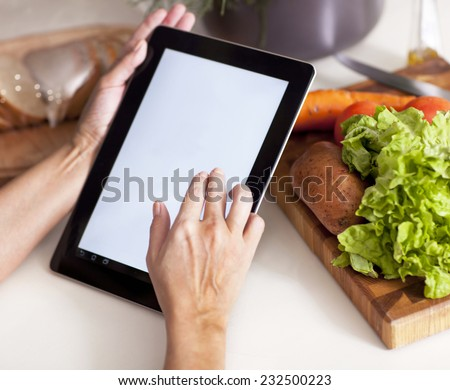 Hands typing on tablet computer in kitchen  - stock photo