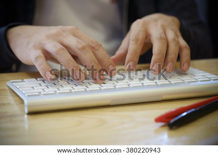 Hands typing on the remote wireless computer keyboard - stock photo