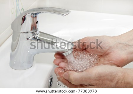 hands under a stream of water from the stop-cock - stock photo