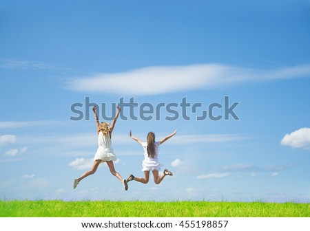 Hands up. rear view of Two teenage girls jumping against summer field with fresh summer green grass and sunny blue sky with clouds . Nature background. No face Unrecognizable person - stock photo