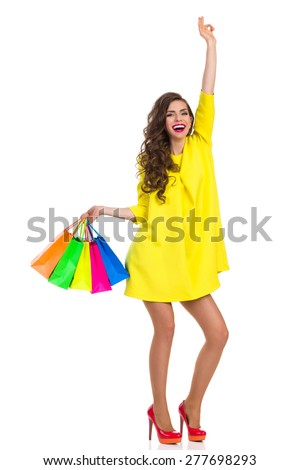 Hands Up Who Goes Shopping With Me. Laughing elegance young woman in red high heels and yellow mini dress holding colorful shopping bags and rising arm. Full length studio shot isolated on white. - stock photo