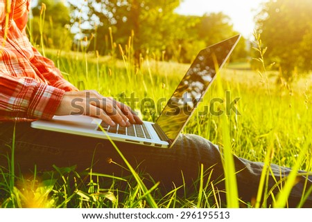 Hands using laptop and typing in summer grass - stock photo