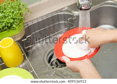 Hands washing the dishes on soapy water - stock photo