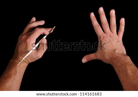 Hands with a brush. Over black empty canvas, drawing imitation - stock photo
