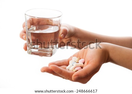 Hands with a glass of water and medicines - stock photo