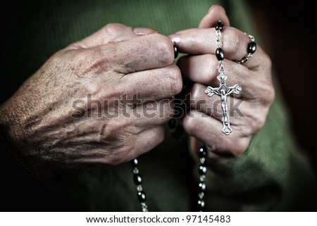 hands with classic catholic rosary - stock photo