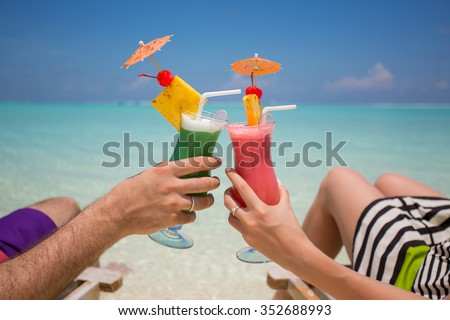 Hands with colorful cocktails on the beach.  - stock photo
