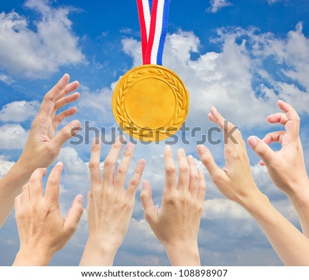 Hands with golden  medal in front of blue sky. - stock photo