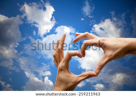 Hands with heart shape on the sky  - stock photo