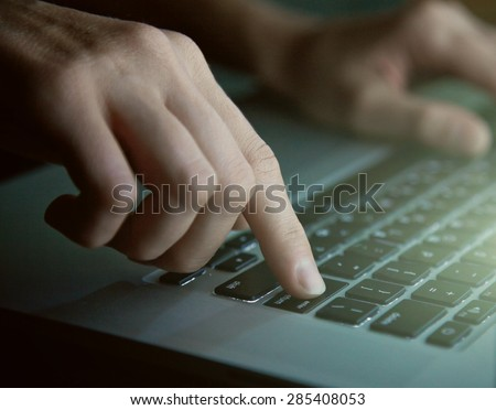 hands with laptop in night pressing enter button - stock photo