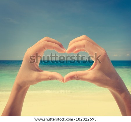 hands with love sign on beach, vintage retro filter  - stock photo