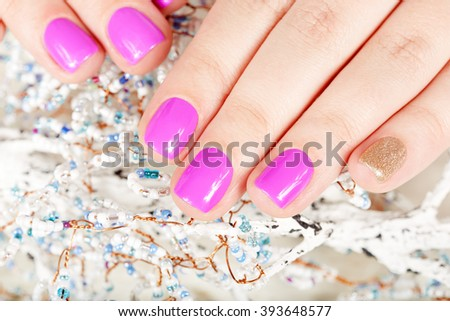 Hands with manicured nails covered with pink and gold nail polish - stock photo