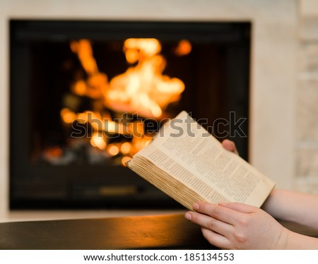 Hands with open book near the fireplace - stock photo