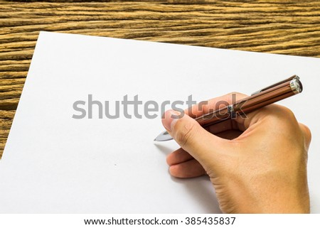 Hands with pen over paper on wooden background. - stock photo