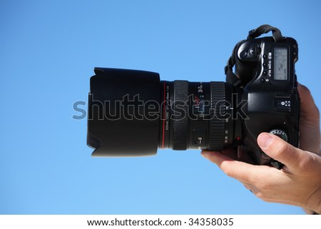 hands with photo camera on sky - stock photo