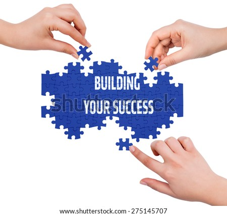 Hands with puzzle making BUILDING YOUR SUCCESS word  isolated on white  - stock photo