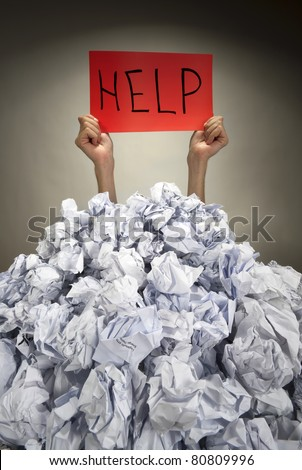 Hands with red frame reaches out from big heap of crumpled papers - stock photo