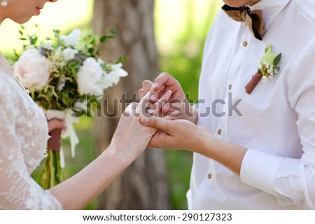 Hands with rings Groom putting golden ring on bride's finger during wedding ceremony - stock photo